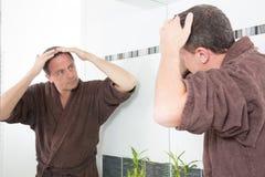 Equipe a queda de cabelo dos controles no banheiro que olha em um espelho imagens de stock royalty free
