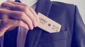 Equipe a remoção de um cartão com os ícones do contato do bolso de seu ja Imagem de Stock
