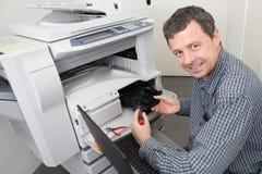 Equipe a reparação de uma impressora no lugar do negócio no trabalho Imagens de Stock Royalty Free