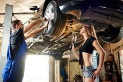 Equipe a reparação do carro no elevador hidráulico, mulher ajuda-o fotos de stock royalty free