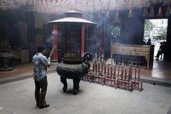 Equipe rezar no templo enchido fumo do incenso em Ho Chi Minh City Imagens de Stock Royalty Free