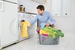Equipe a roupa da carga na máquina de lavar Fotografia de Stock Royalty Free