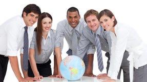 Equipe séria do negócio em torno de um globo terrestre