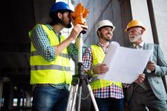 Equipe segura dos arquitetos e dos coordenadores que trabalham junto no canteiro de obras imagem de stock