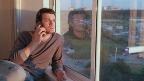 Equipe seletores o número e as esperas de telefone para uma resposta que senta-se no balcão no por do sol vídeos de arquivo