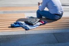 Equipe senta-se em um banco e usa-se um telefone celular imagens de stock royalty free