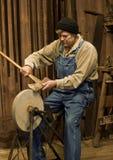 Equipe sharpening um machado em uma pedra de moedura Foto de Stock