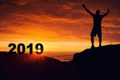 Equipe a silhueta na parte superior da montanha que olha o nascer do sol e o 2018 fotos de stock royalty free