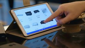 Equipe a site de exploração de IKEA que procura a mobília usando o PC da tabuleta no café filme