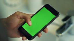 Equipe smartphone tocante com a tela do verde da chave do croma Vista no teclado e na tela video estoque