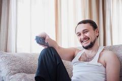 Equipe sorrisos e posses o telecontrole em sua mão Foto de Stock