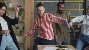A equipe start-up fêmea e masculina do grupo diverso do negócio tem a dança do divertimento no escritório moderno e sucesso da co vídeos de arquivo