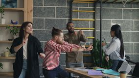 A equipe start-up fêmea e masculina do grupo diverso do negócio tem o partido de dança do divertimento em originais de papel de j filme