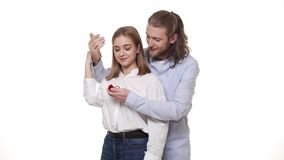 Equipe surpreendente seu sócio com anel de noivado sobre o fundo branco isolado filme