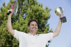 Equipe a sustentação de raquetes de tênis e de troféu na opinião de baixo ângulo do campo de tênis foto de stock royalty free