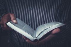 Equipe a sustentação de uma Bíblia aberta em suas mãos fotos de stock royalty free