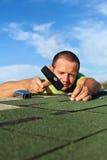 Equipe telhas do telhado do betume da asseguração com pregos e martelo Imagem de Stock Royalty Free