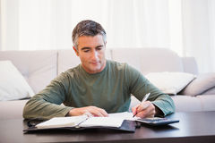 Equipe a tomada de notas com calculadora e bloco de notas na tabela Fotos de Stock Royalty Free