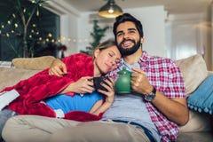 Equipe tomar de sua amiga doente que encontra-se no sof? foto de stock