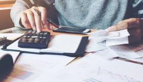 Equipe usando a calculadora e calcule contas no escritório domiciliário fotos de stock royalty free