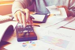 Equipe usando a calculadora e calcule o custo com guardar a conta no hom fotografia de stock royalty free