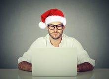 Equipe usando o laptop que compra em linha procurando um presente do Natal Imagem de Stock Royalty Free