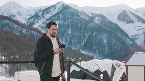 Equipe usando o móbil para enviar a mensagem, estando fora na base do esqui nas montanhas filme