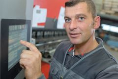 Equipe usando o PC da tabuleta contra equipamentos industriais na fábrica fotos de stock