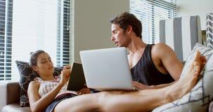 Equipe usando o portátil e a mulher que leem um livro na sala de visitas 4k video estoque