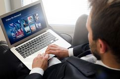Equipe usando o portátil para o filme de observação no serviço de VOD Imagem de Stock