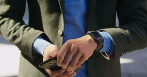 Equipe usando o telefone celular e o smartwatch na rua 4k filme