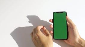 Equipe usando o telefone com a tela verde no fundo branco filme