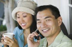 Equipe usando o telefone móvel e a mulher com bebida Imagens de Stock Royalty Free