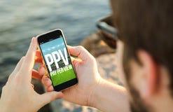 Equipe usando seu telefone celular no pay per view da costa Imagens de Stock Royalty Free