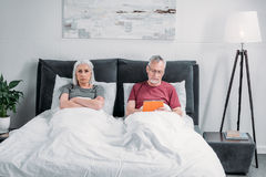 Equipe usando a tabuleta quando esposa mal-humorada que encontra-se na cama fotografia de stock