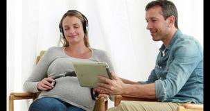 Equipe usando a tabuleta quando música de escuta da mulher gravida em fones de ouvido video estoque
