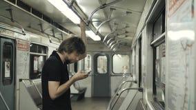 Equipe a utilização móvel e a datilografia de um telefone da mensagem no vagão do metro, wi fi do público do transporte do metro  vídeos de arquivo