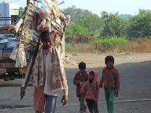 Equipe a venda de brinquedos na estrada com suas crianças que andam atrás dele Fotografia de Stock Royalty Free