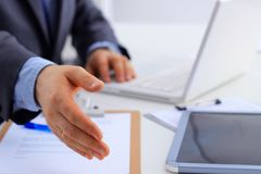 Equipe vestir um terno que oferece agitar as mãos, sentando-se na mesa imagens de stock royalty free