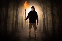 Equipe a vinda da floresta escura com a tocha ardente em seu conceito da m?o imagens de stock