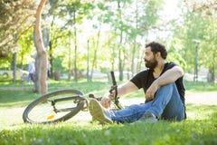 Equipe a vista ausente ao descansar na grama no parque imagem de stock