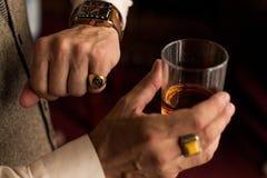 Equipe a vista de seu relógio à moda na mão esquerda com um anel no dedo pequeno No assistente ele que guarda um vidro do uísque fotos de stock