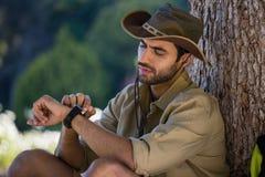 Equipe a vista de seu relógio de pulso ao descansar perto da árvore fotos de stock