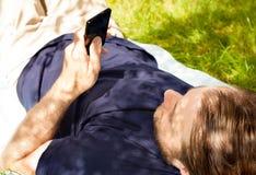 Equipe a vista do telefone celular ao colocar na grama foto de stock