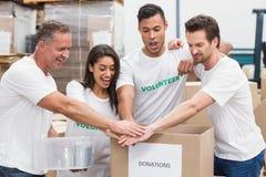 Equipe voluntária que guarda as mãos em uma caixa das doações Fotografia de Stock Royalty Free