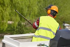 Equiped worker pruning a tree on a crane. Gardening. Works Royalty Free Stock Photo