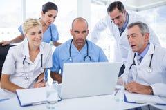 Equipes dos doutores que trabalham no laptop Imagem de Stock Royalty Free