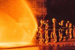Equipes dos sapadores-bombeiros que trabalham em um fogo Imagens de Stock Royalty Free