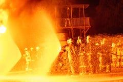 Equipes dos sapadores-bombeiros que trabalham um fogo Imagens de Stock Royalty Free