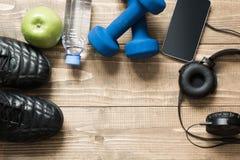 Equipmen de sport et de forme physique avec des espadrilles, des haltères, la serviette et des écouteurs sur le conseil en bois V Photographie stock libre de droits